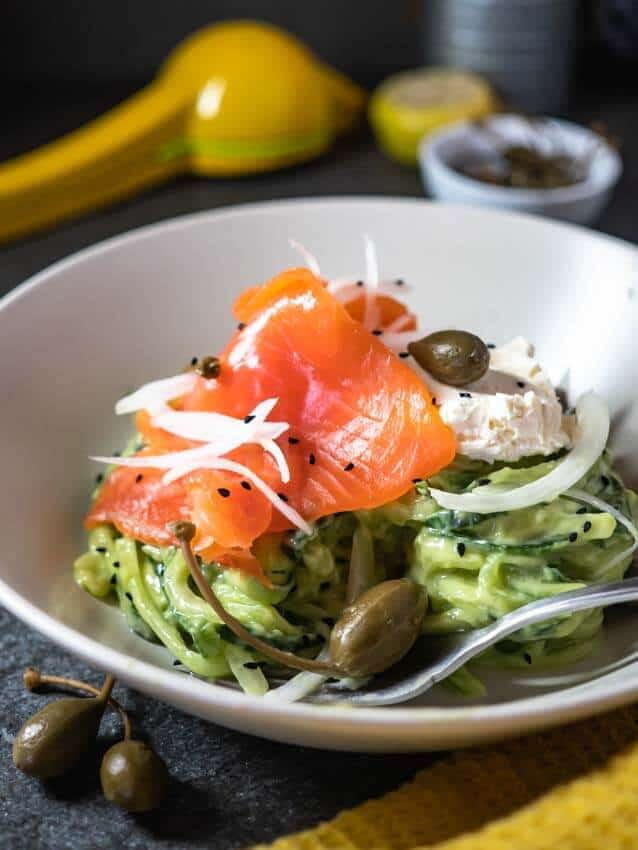 Low side shot of avocado cucumber noodles in a white bowl topped with smoked salmon, cream cheese, onion and caper berries