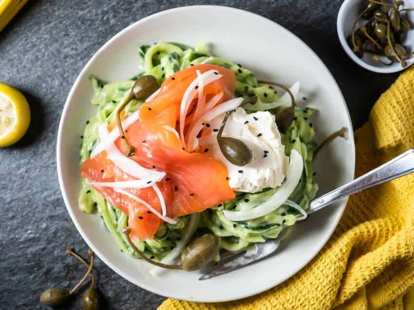 Top shot of a white bowl filled with avocado cucumber noodles, smoked salmon, cream cheese and caper berries. It sits on a grey background with a yellow rag and a small bowl of caper berries