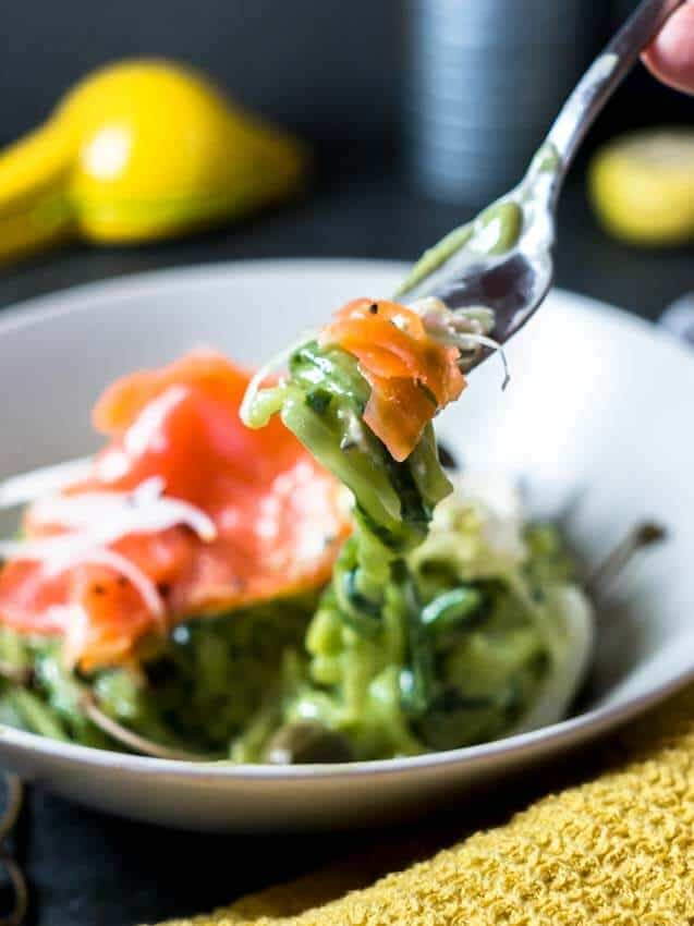 Side shot of a fork twisting cucumber noodles with a white bowl in the background filled with Avocado Cucumber Noodles and Smoked Salmon