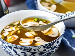 Close up high side shot Japanese Clear Onion Soup in a white and blue patterned bowl with a spoon scooping a bite.