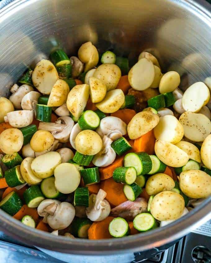 top shot of a stainless steel pot with with vegetables. mushrooms, potatoes, zucchini, carrots.