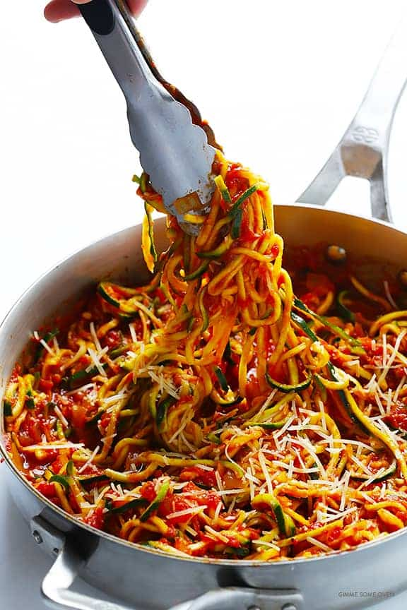 Zucchini spaghetti marinara in a gray skillet with a white background.