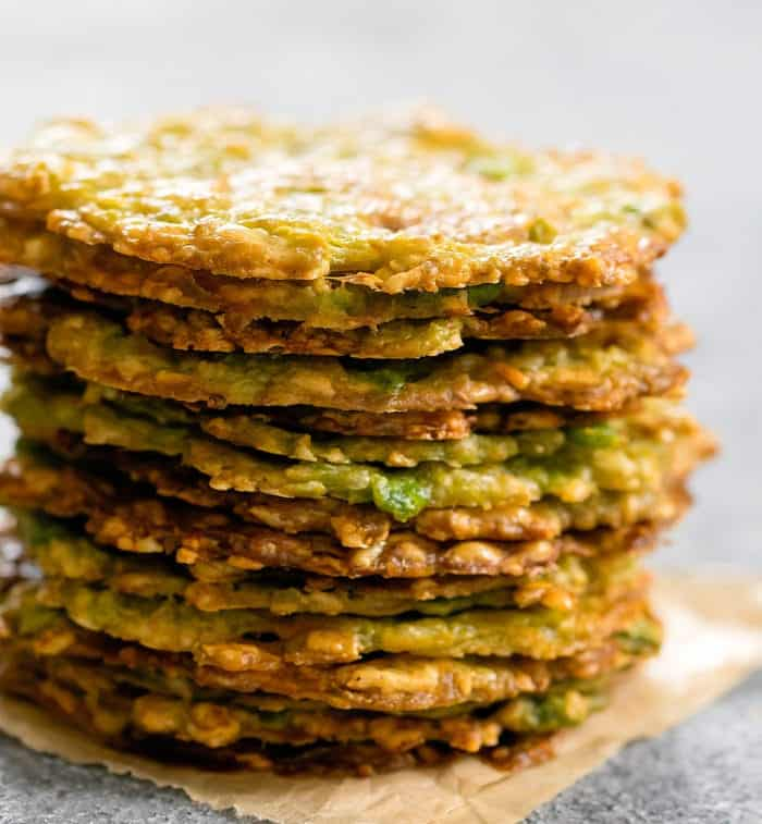 Baked keto avocado chips stacked on a gray surface.