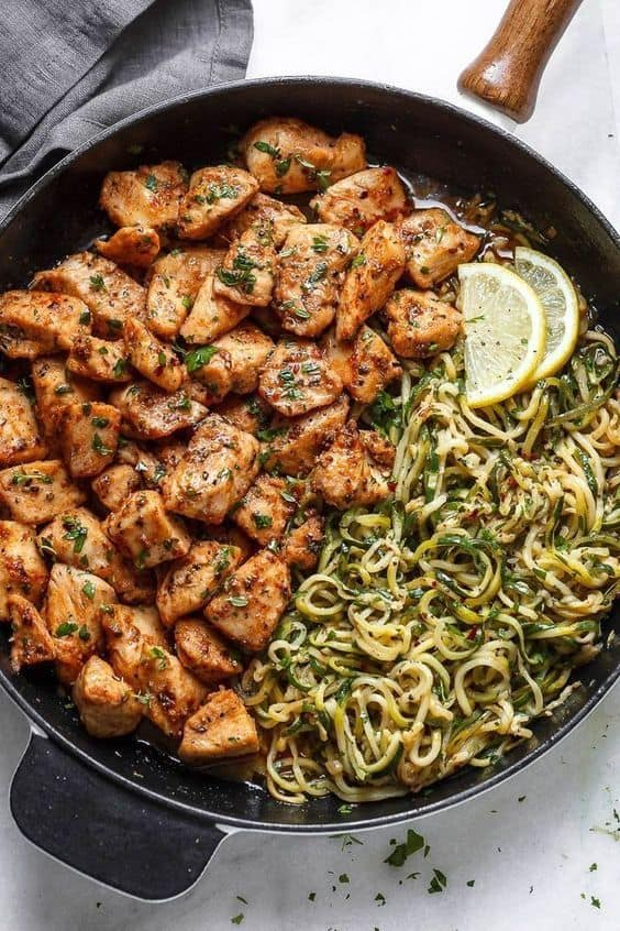 Garlic butter chicken bites with lemon zucchini spaghetti topped with fresh herbs in a black skillet on a white background.