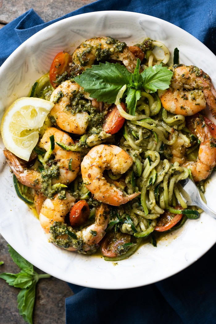 Keto zucchini spaghetti with pesto and shrimp topped with fresh herbs in a white bowl in a blue background.