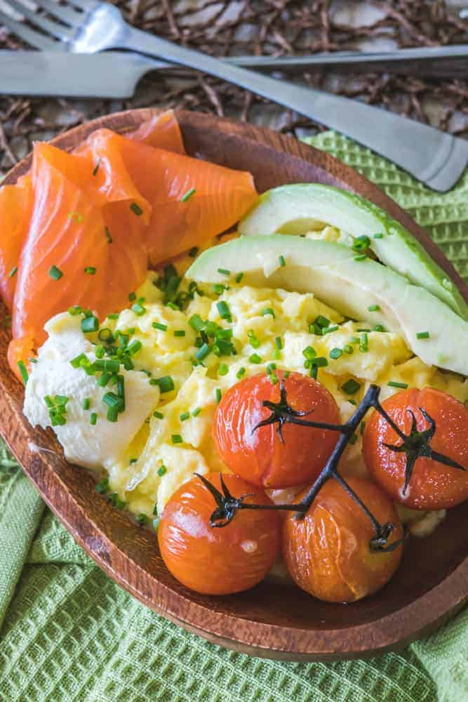 Smoked salmon, avocado, scrambled egg, and vine tomatoes topped with fresh chopped chives in a wooden bowl on a green kitchen towel.