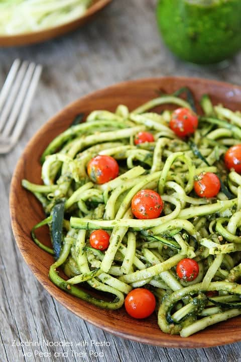 Zucchini noodles with pesto in a brown bowl on a light brown wooden background.