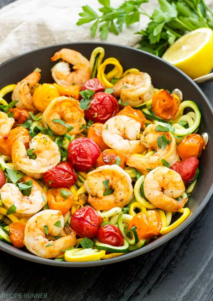 Zucchini spaghetti with shrimp and roasted tomatoes in a black bowl on a black background.