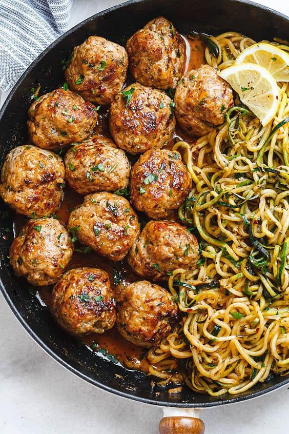 Garlic butter zucchini spaghetti and meatballs topped with fresh herbs in a black skillet on a white background.