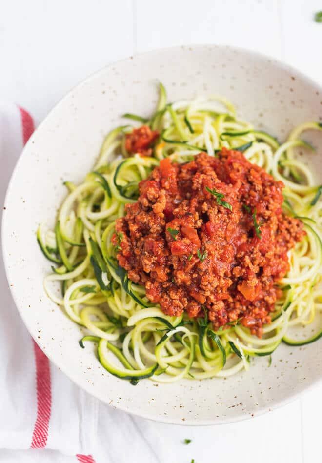 Zucchini spaghetti bolognese in a white bowl on a white background.