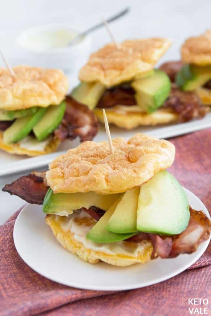 Bacon and avocado cloud bread sandwich in a white plate on a red kitchen towel.