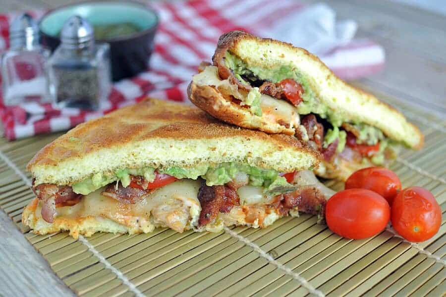 Bacon, avocado, and chicken cloud bread sandwich on a bamboo mat.