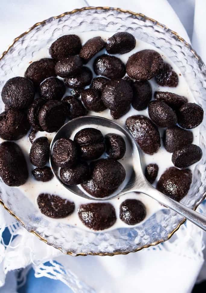 Cocoa puffs keto breakfast cereal in a glass bowl with a white background.