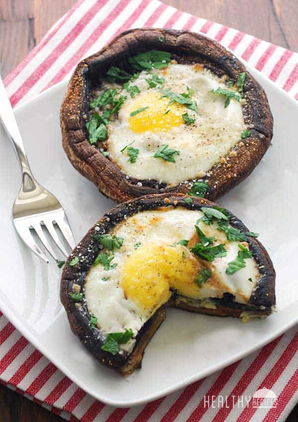 Breakfast eggs baked in portobello mushrooms topped with fresh herbs in a white plate on a striped kitchen towel.