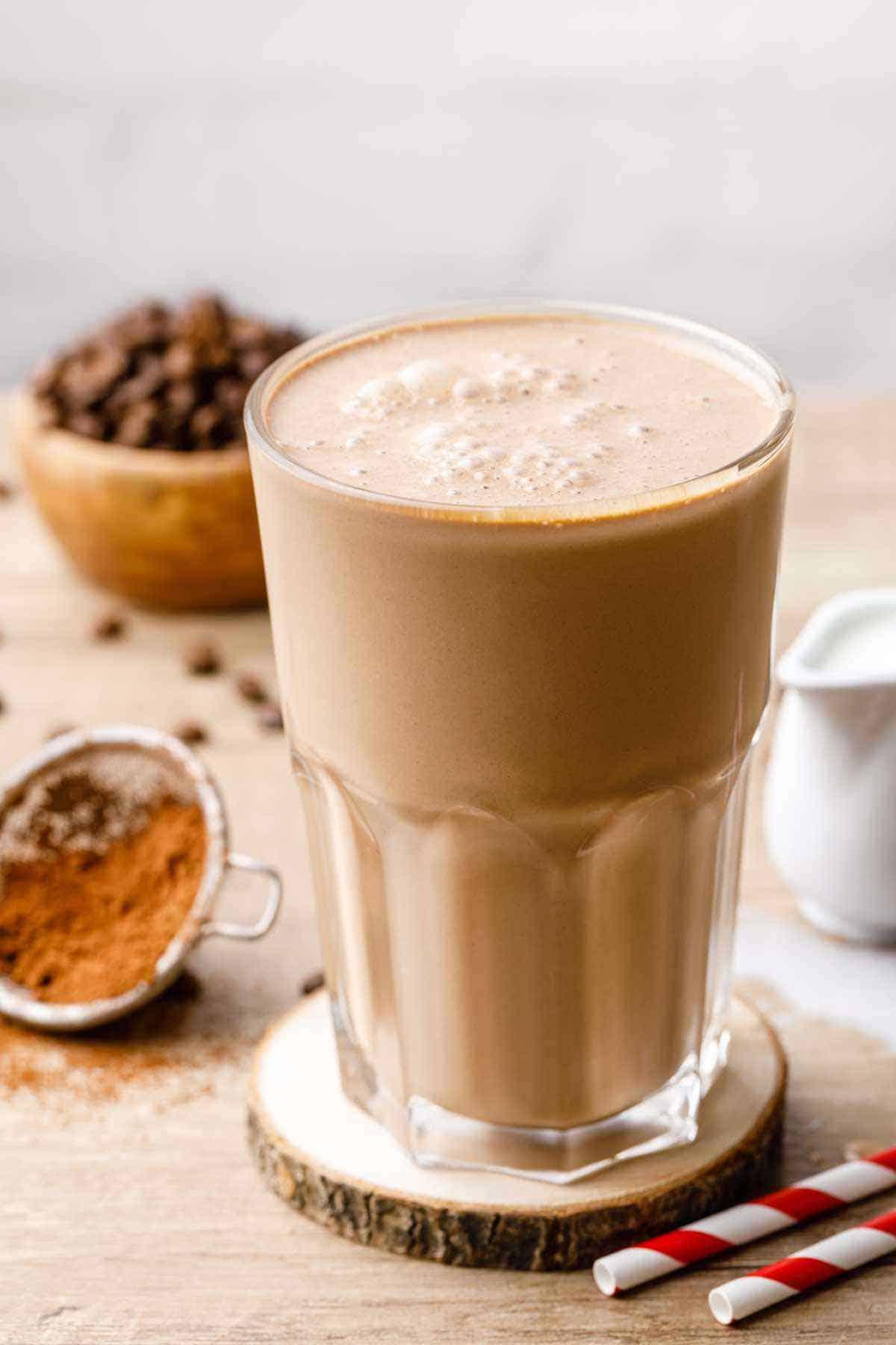 Frozen mocha keto breakfast shake on a wood table surrounded by fresh ingredients.