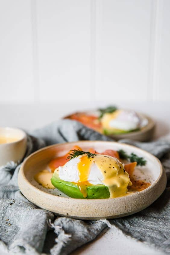 Keto breakfast eggs benedict with avocado topped with hollandaise sauce in a beige plate on a gray background.
