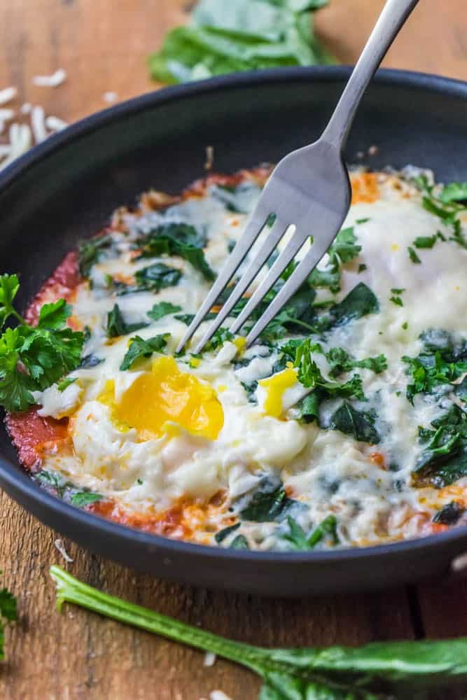 Italian eggs keto breakfast topped with fresh herbs in a black bowl on a brown wooden background.