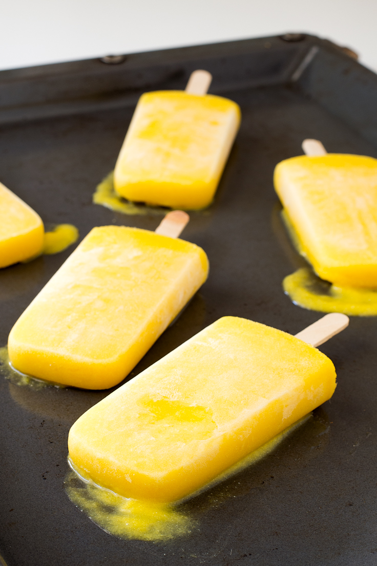 bright yellow mango coconut popsicles on a dark grey metal tray