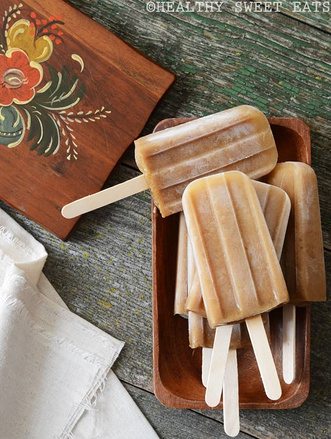 a stack banana chai popsicles on a wooden tray