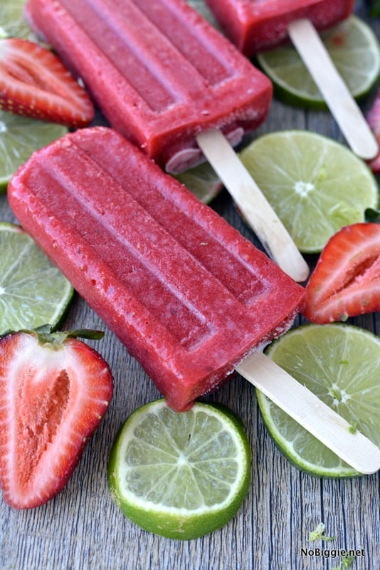 bright red strawberry popsicles on a wooden surface with fresh sliced strawberries and limes