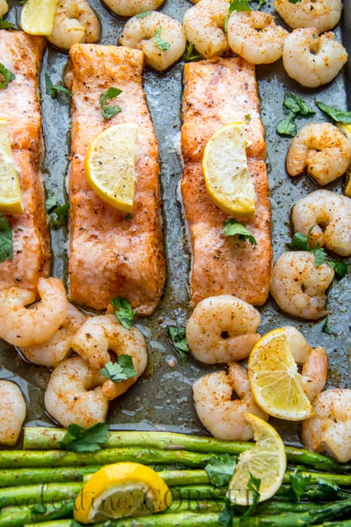 Baked Shrimp Salmon and Asparagus on a sheet pan garnished with lemon slices and fresh herbs