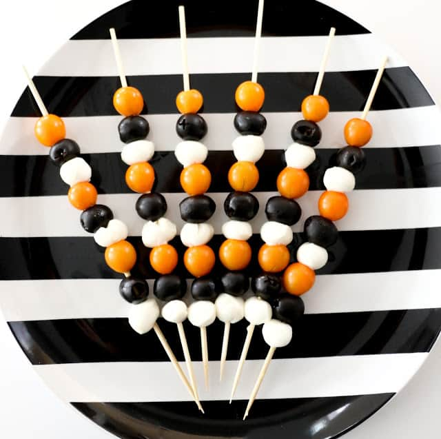 Healthy Halloween antipasto skewers arranged on a striped black and white plate with a white background.