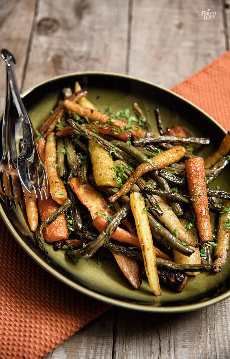 Balsamic roasted carrots and green beans topped with fresh herbs in a green plate on a wooden surface.