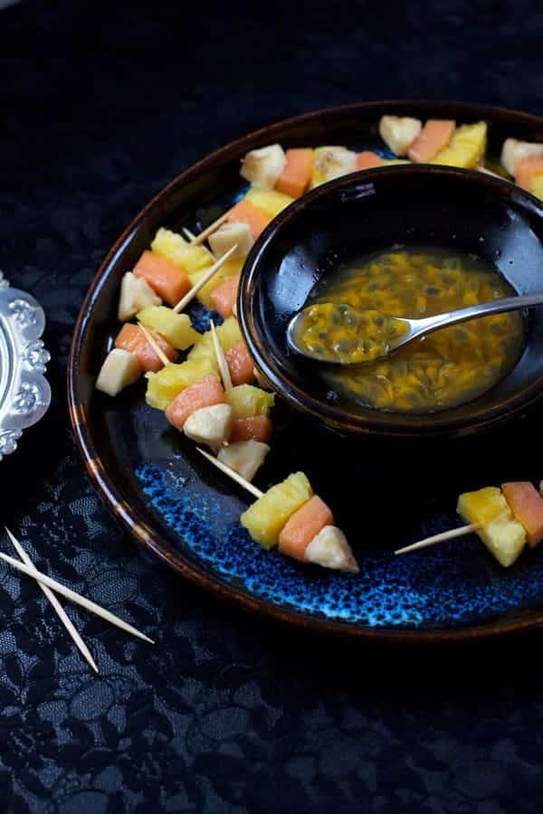 Healthy Halloween candy corn kebabs arranged around a granadilla sauce with a dark blue background.