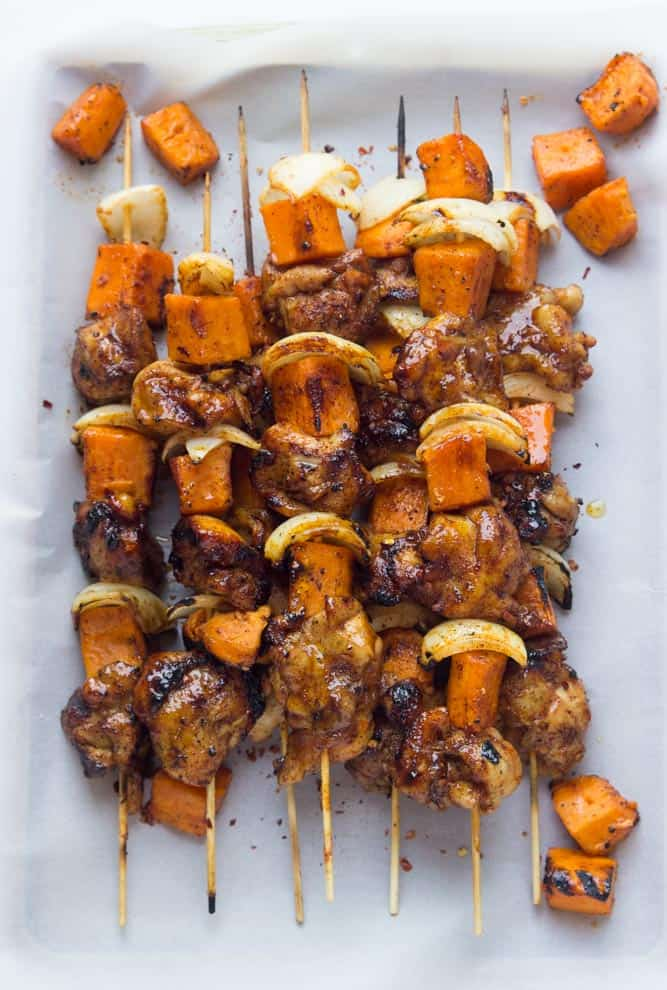 Spicy honey-glazed chicken and sweet potato kebabs stacked on a white baking sheet.
