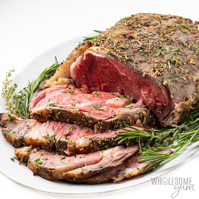 Garlic butter prime rib roast cut in slices topped with fresh herbs in a white serving plate with a white background.