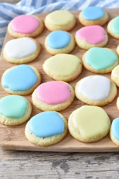 Keto Christmas cookies with colored icing displayed on a wooden platter.