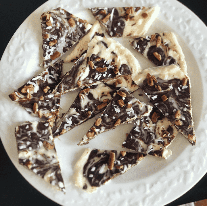 Keto Christmas crack peppermint bark pieces in a white plate on a black surface.