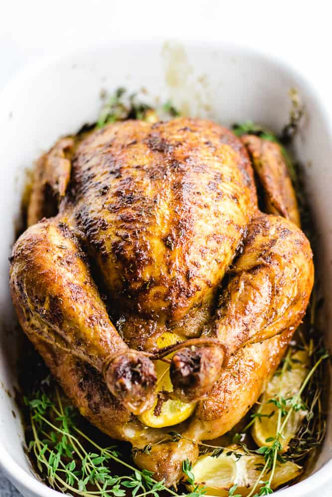 Low-Carb Christmas roast chicken surrounded by herbs in a square white baking dish.