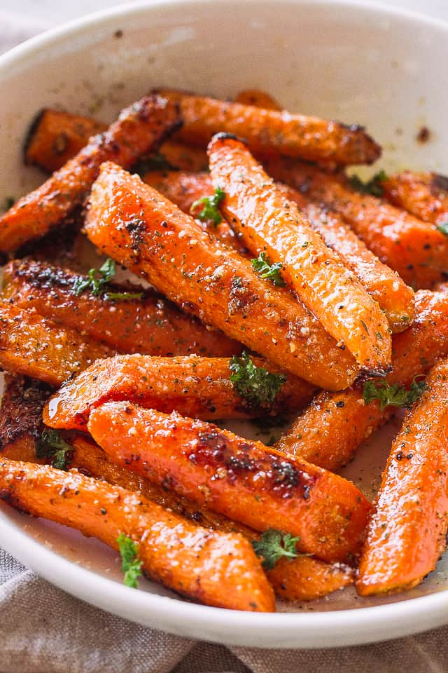 Roasted garlic parmesan carrots topped with herbs in a white bowl.