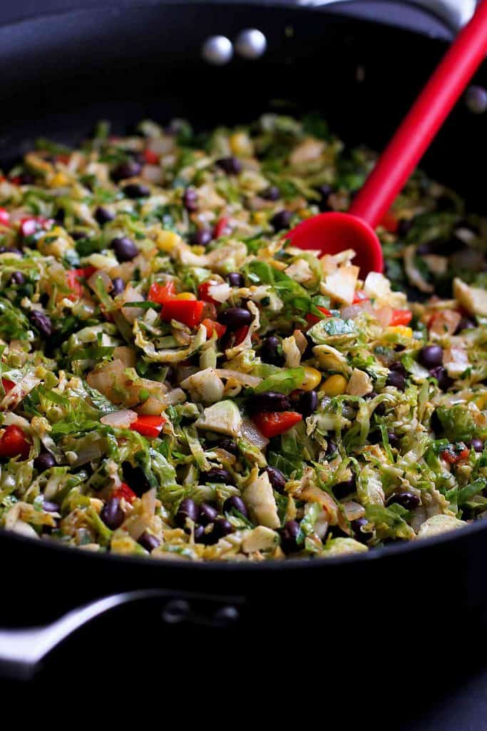 Shredded brussels sprouts with beans and chopped vegetables in a black pot.