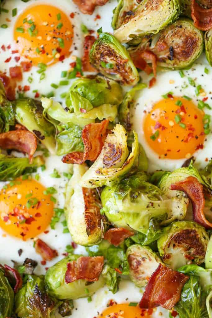 Chopped brussels sprouts, fried eggs and bacon pieces topped with fresh chopped chives.