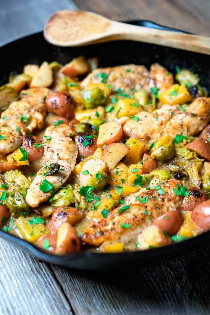 Creamy chicken, potatoes and brussels sprouts topped with fresh chopped herbs in a black skillet on a wooden background.