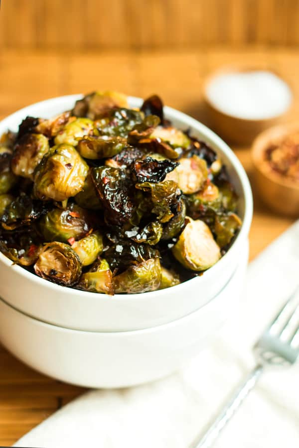 Chopped brussels sprouts with honey mustard sauce in a white bowl on a wooden background.