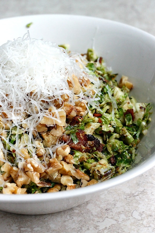 Shredded brussels sprouts topped with bacon pieces, chopped nuts and shredded cheese in a white bowl on a gray background.