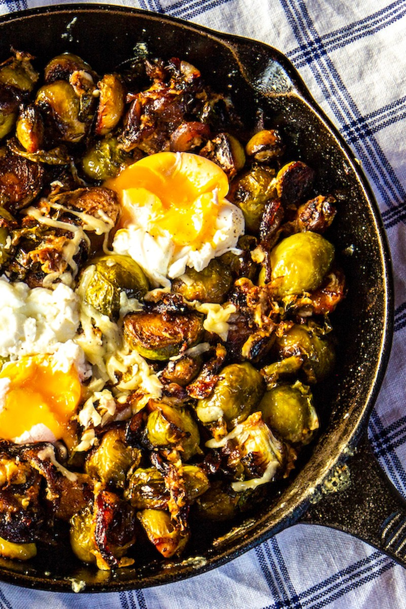 Brussels sprouts, caramelized onions and fried eggs in a black skillet on a blue and white kitchen towel.