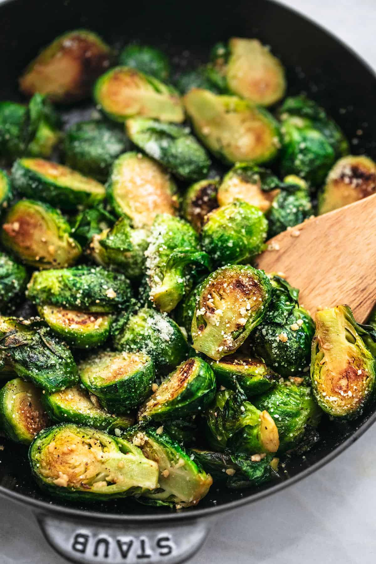 Halved brussels sprouts covered in powdered parmesan in a black skillet.