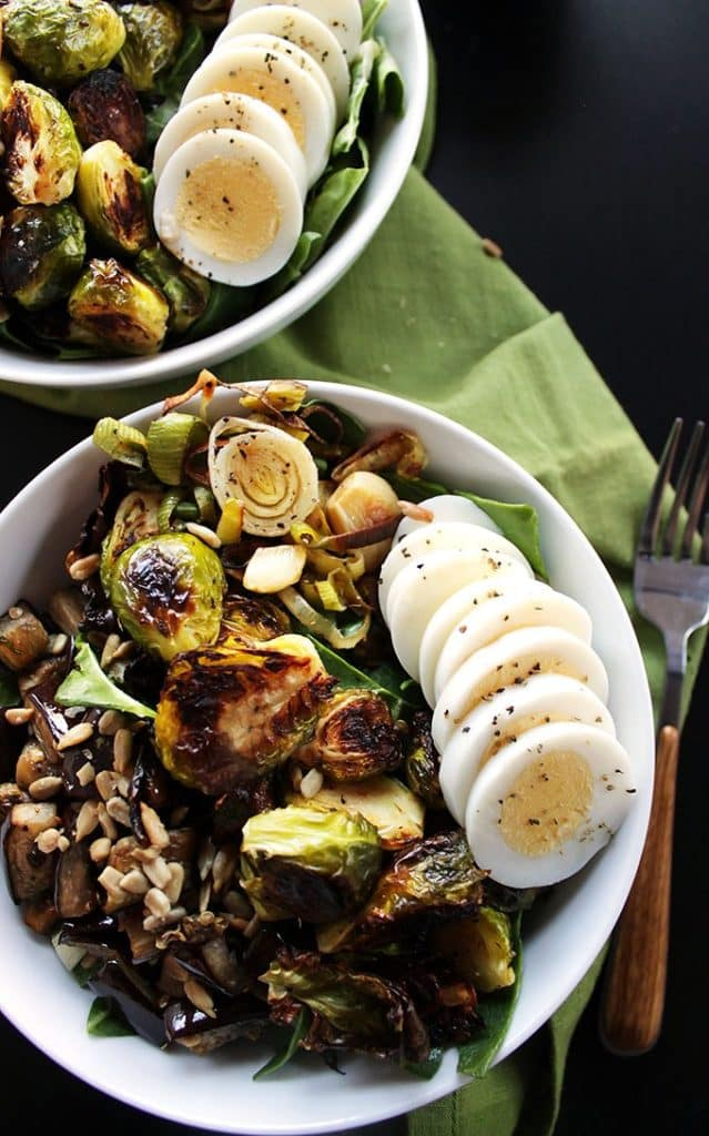 Brussels sprouts and eggplant buddha bowls on a black background.