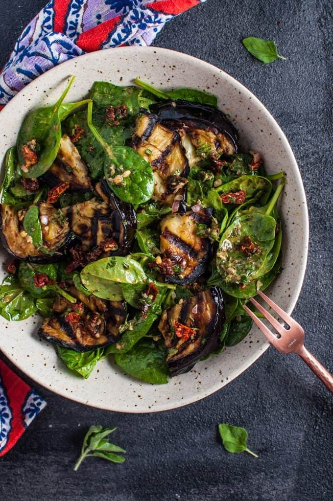Grilled eggplant and spinach salad in a white bowl on a dark gray background.