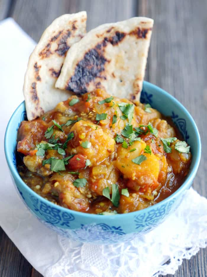 Indian eggplant curry topped with fresh herbs in a blue bowl on a wooden background.