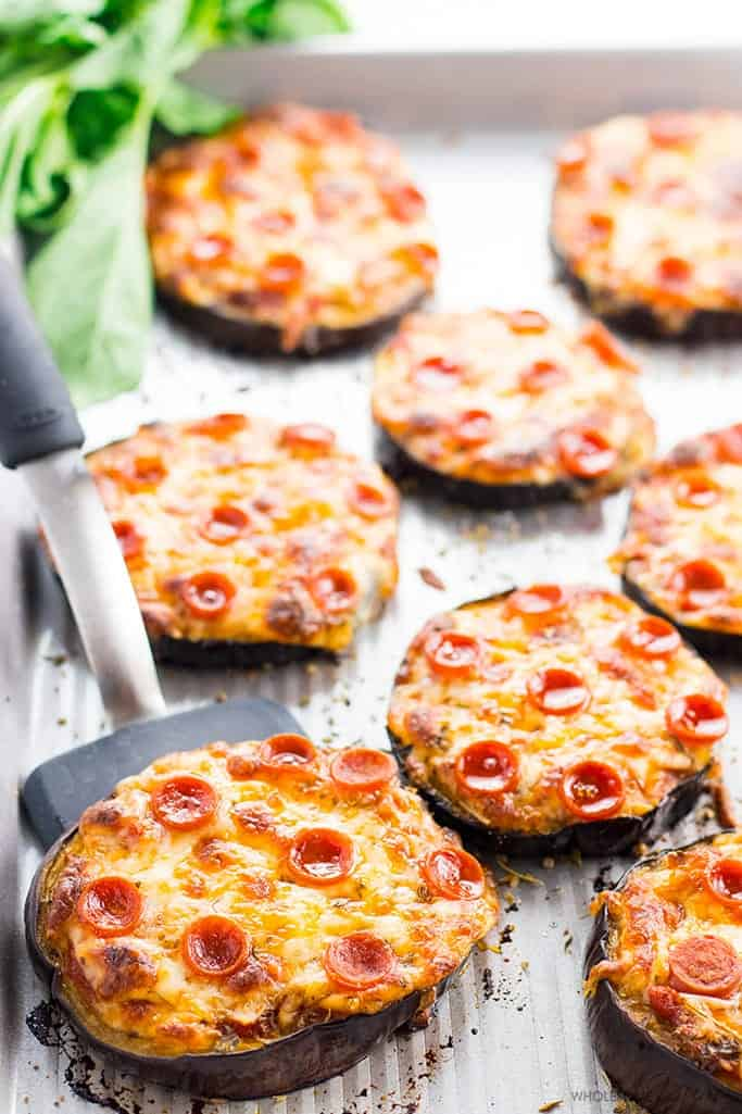 Eggplant pizza slices topped with pepperoni on a gray platter.