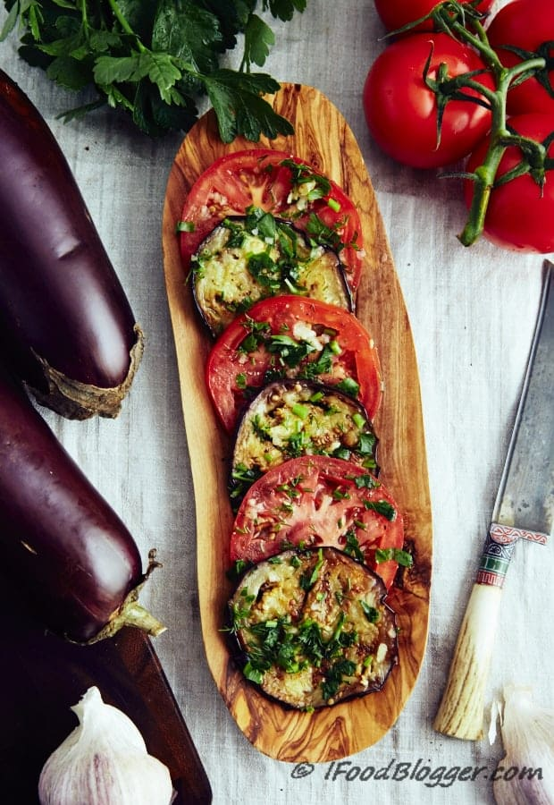 Marinated eggplant and tomatoes topped with fresh herbs on a wooden platter on a white kitchen towel surrounded by fresh vegetables.
