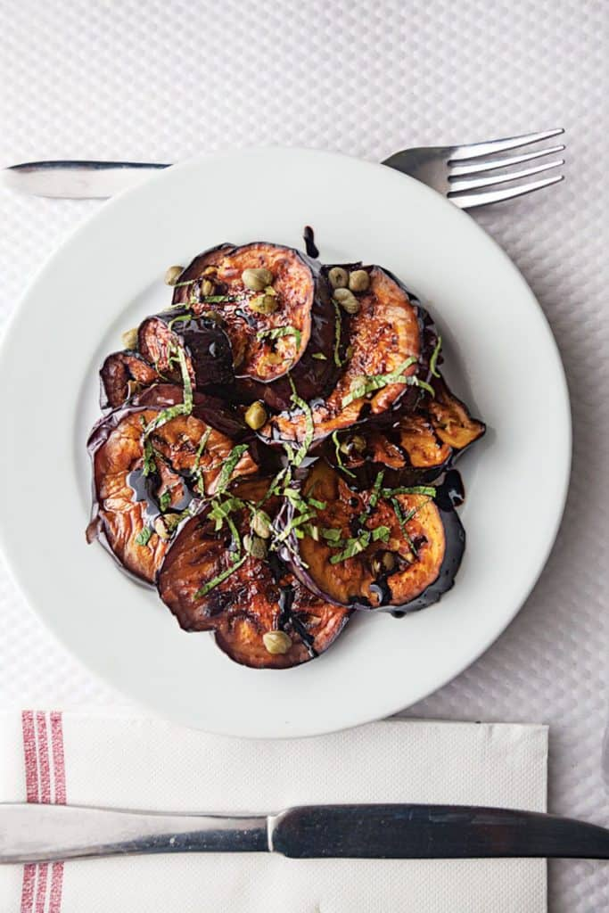 Pan fried eggplant topped with fresh herbs in a white plate on a white background.