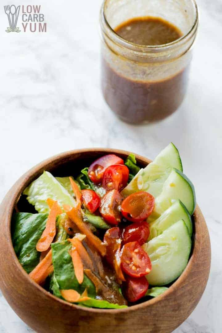 Fresh salad in a wood bowl with olive oil and balsamic dressing in a glass jar in the top right corner on a white background.