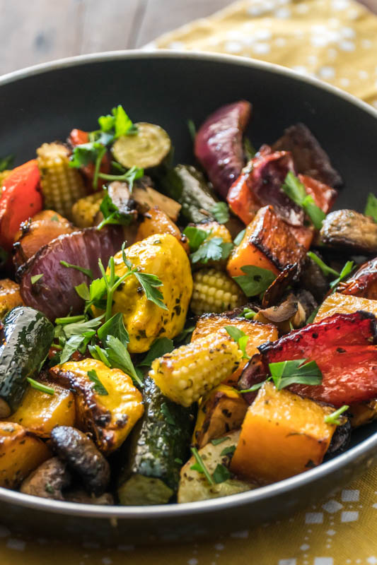 Top shot of chimichurri oven roasted vegetables, topped with fresh herbs, in a black bowl placed on a yellow kitchen towel.