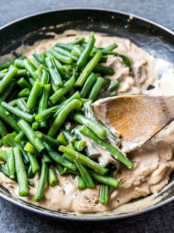 Close up shot of cooked green beans tossed on top of creamy mushrooms in a pan. A wooden spoon stirring